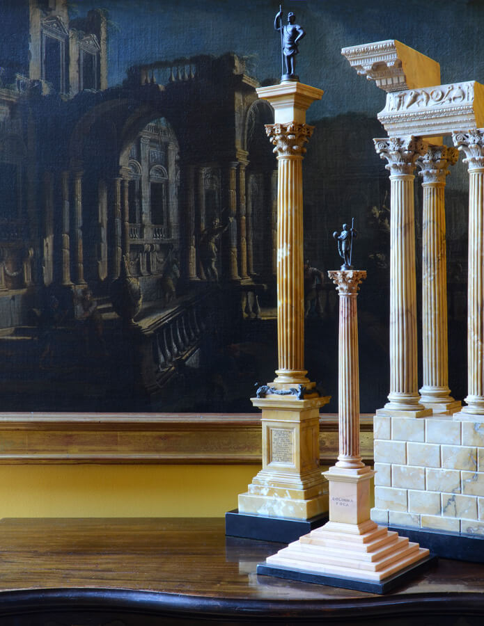 Three large Grand Tour models made of giallo antico, antique yellow Roman marble, before Pietro Cappelli's 18th century capriccio painting with similar columns.