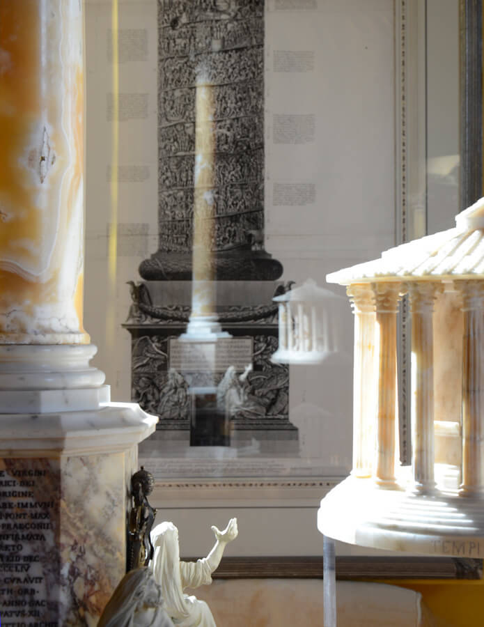 In PIraneseum's Grand Tour Model Gallery, alabaster temples, and a variety of marble replicas are shown against a background of Piranesi prints.